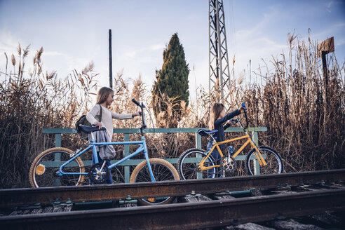 Two girls walking on the train track with bicycles - OCMF00188