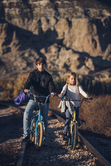 Boy and girl on the train track with bicycles - OCMF00191