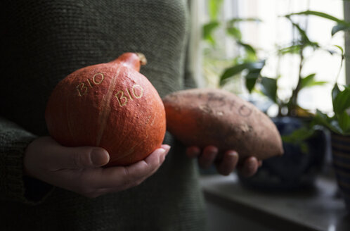 Woman's hands holding organic Hokkaido pumpkin and sweet potatoe with Smart Branding - MAMF00294