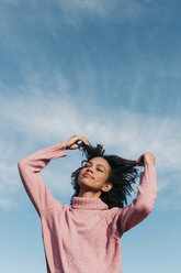 Afro woman wearing a pink jumper touching her hair with the blue sky behind. Mallorca, Balearic Islands, Spain. - LOTF00033