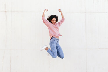 Happy young woman jumping in the air against light background - LOTF00036