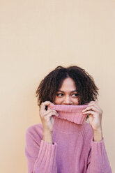 Young woman with afro hair covering her face with a pink turtleneck jumper. Studio shot. - LOTF00042