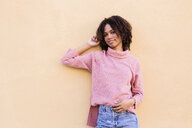 Portrait of smiling young woman wearing pink turtleneck pullover leaning against wall - LOTF00045