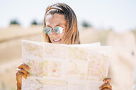 Blond young woman wearing mirrored sunglasses orientating with map - OCMF00201