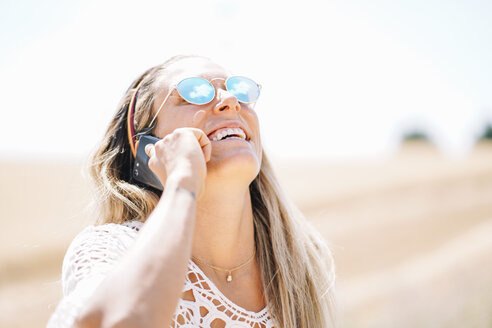 Smiling young woman on the phone wearing mirrored sunglasses looking up - OCMF00204
