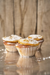 Three muffins with candied orange slice and icing sugar on top - EPF00530