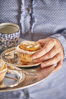 Woman's hand holding muffin with candied orange slice on silver platter - EPF00533