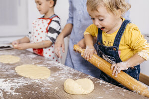 Excited toddler girl rolling out dough with wooden rolling pin - JRFF02348