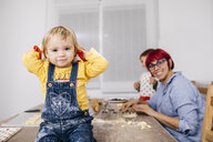 Portrait of smiling toddler girl sitting on kitchen table where mother and brother preparing cookies - JRFF02354