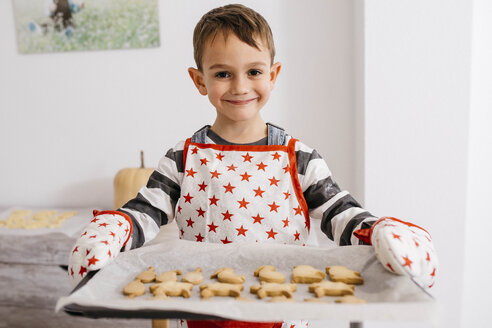 Portrait of smiling little boy holding baking tray with home-made cookies - JRFF02357