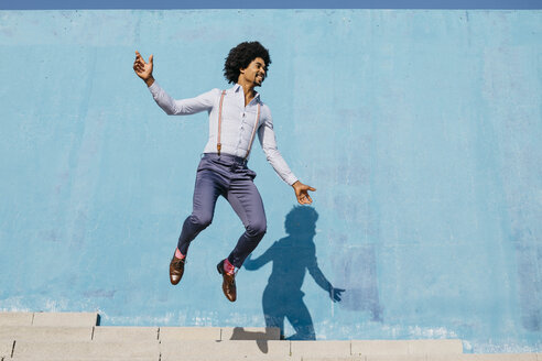 Smiling man jumping in the air in front of blue wall - JRFF02409