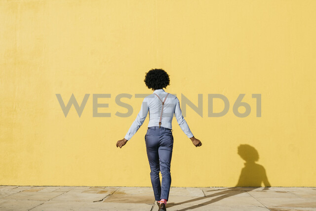 Back view of man wearing suspenders dancing in front of yellow wall - JRFF02412 - Josep Rovirosa/Westend61