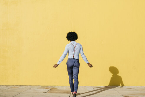 Back view of man wearing suspenders dancing in front of yellow wall - JRFF02412