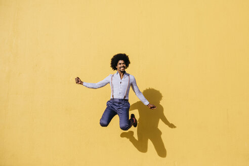 Smiling man jumping in the air in front of yellow wall - JRFF02415
