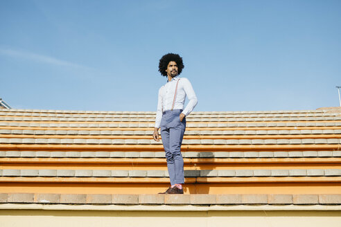Stylish man standing on stairs - JRFF02421