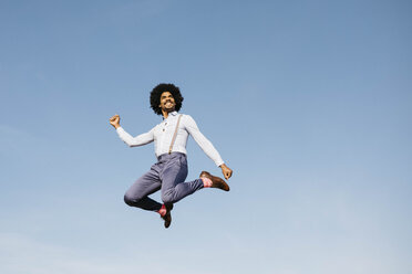 Smiling man jumping in the air against blue sky - JRFF02424