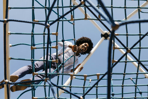 Spain, Barcelona. Afro man smiling raised in a play structure for children. - JRFF02433