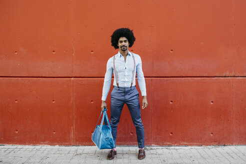Portrait of fashionable man with bag standing in front of a red wall - JRFF02439