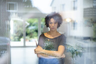 Portrait of woman standing behind window at home - JOSF02673