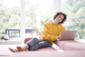 Smiling woman using laptop on couch at home - JOSF02685