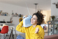 Carefree woman listening to music with portable radio at home - JOSF02688