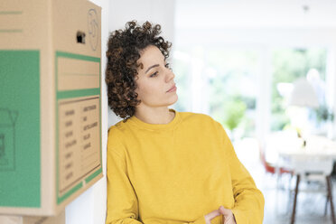 Serious woman leaning against a wall at home with cardboard boxes - JOSF02691