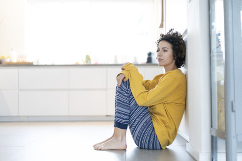 Serious woman sitting on floor leaning against a wall at home - JOSF02694