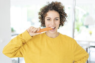 Portrait of woman eating a carrot at home - JOSF02697