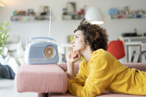 Woman lying on couch listening to music with portable radio at home - JOSF02700