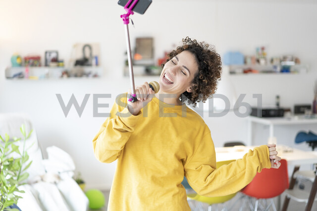 Carefree woman at home singing into microphone attached to a selfie stick - JOSF02703 - Joseffson/Westend61
