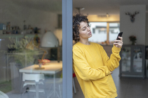 Woman leaning against terrace door at home checking cell phone - JOSF02709