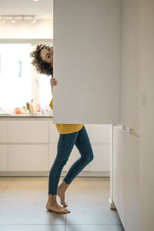 Portrait of woman at the fridge in kitchen at home - JOSF02718