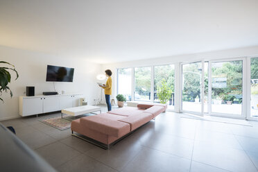 Woman using laptop in a spacious living room at home - JOSF02727