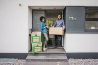 Couple standing at house entrance with cardboard boxes - JOSF02733