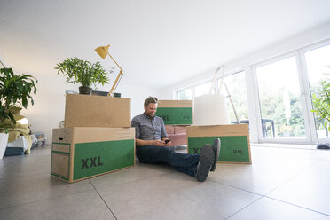 Man sitting in living room surrounded by cardboard boxes using cell phone - JOSF02736