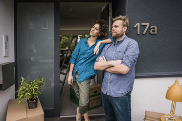 Couple standing at house entrance with cardboard boxes - JOSF02742