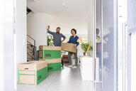 Portrait of couple in new home with cardboard boxes - JOSF02745