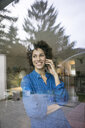 Portrait of smiling woman on cell phone behind window at home - JOSF02748
