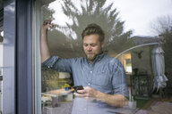 Smiling man checking cell phone behind window at home - JOSF02751