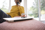 Camper van model on laptop with woman in background - JOSF02754