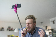 Man at home singing into microphone attached to a selfie stick - JOSF02757