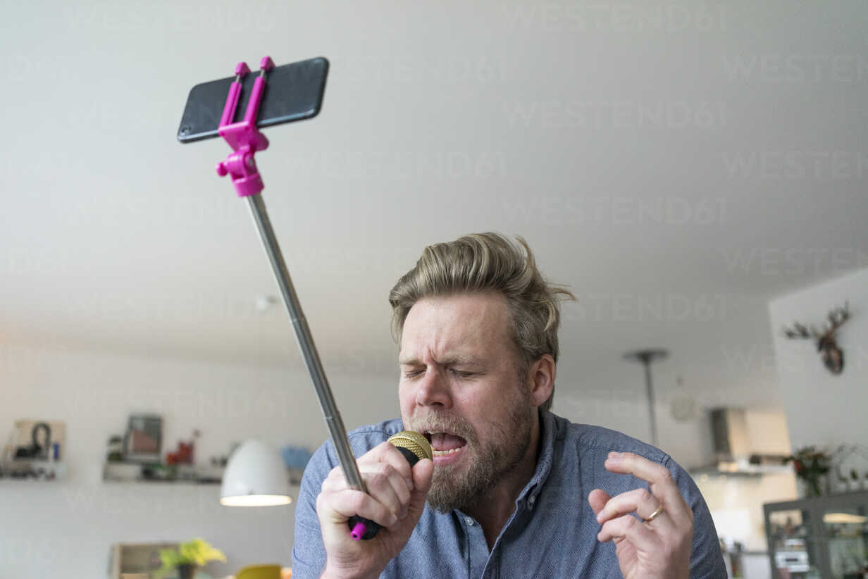 Man at home singing into microphone attached to a selfie stick - JOSF02757 - Joseffson/Westend61