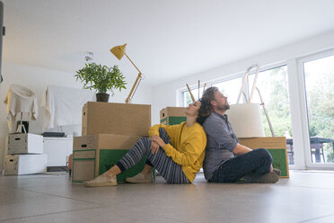 Couple sitting in living room with cardboard boxes - JOSF02760