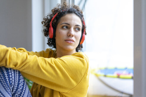 Woman wearing headphones looking out of window - JOSF02763