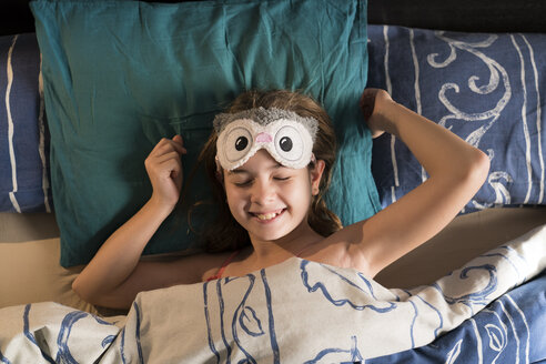 Happy girl lying in bed wearing a mask - XCF00189