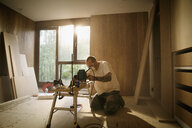 Construction worker using electric saw to cut wood in house - HOXF04250