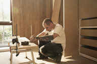 Construction worker with tattoo measuring wood board in house - HOXF04253