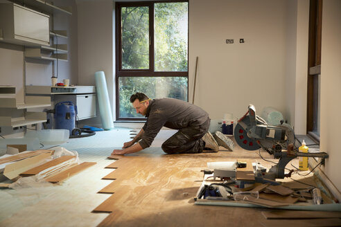 Construction worker laying hardwood flooring in house - HOXF04259