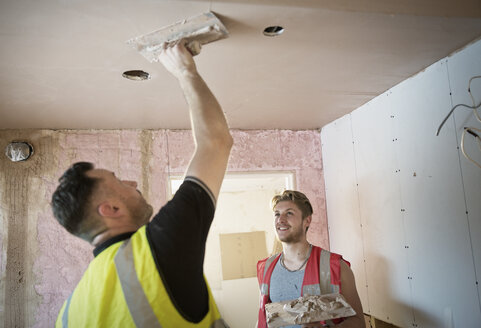 Construction workers plastering ceiling - HOXF04268
