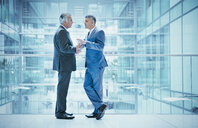 Businessmen talking on modern office atrium balcony - HOXF04286